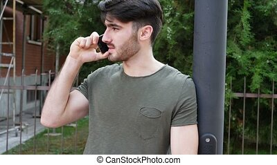 Young man answering call on smartphone outside - Young...