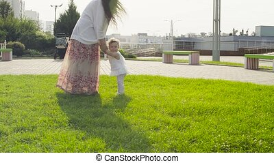 Mom holding baby girl and whirling with her - Mom holding...