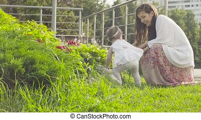 Baby girl looking on the flowers on flower bed - Baby girl...