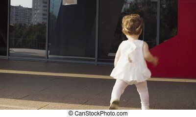 Baby girl running near the shopping center early in the...