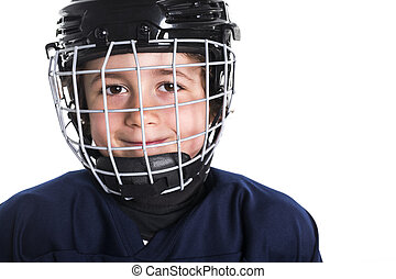 Young boy in ice hockey gear against white - A Young boy in...