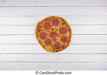 Top view of baking pepperoni pizza on white wood background