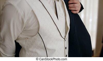 Young man put on the jacket. Closeup shot.