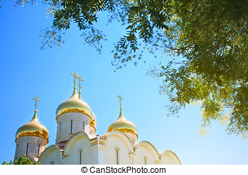 Golden domes of the Orthodox church against the blue sky.