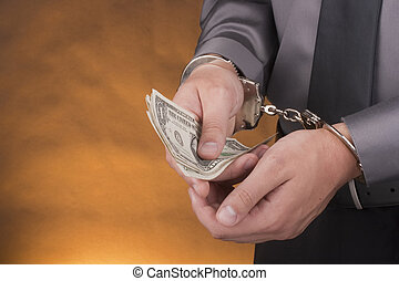 Arrest handcuffs - Arrest, close-up mans hands with money in...