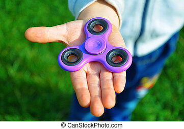 Child holds the spinner in his hand foto