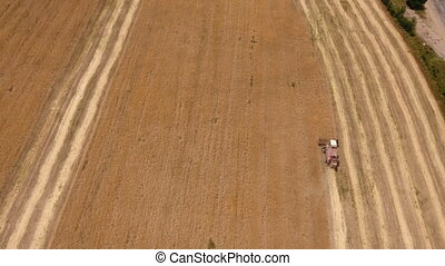 Aerial shot of a combine harvester making numerous long...