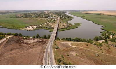 Aerial shot of a wide bridge covering the Dnipro riverbanks...