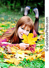 redheaded gril in autumn forest - redheaded gril lating on...