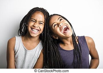 Adorable african twin little girls on studio gray background...