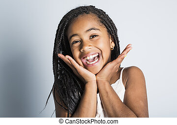 Adorable african little girl on studio gray background - An...