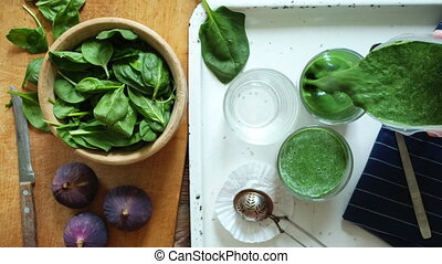 Person pours the smoothie in glass - Overhead view crop of...