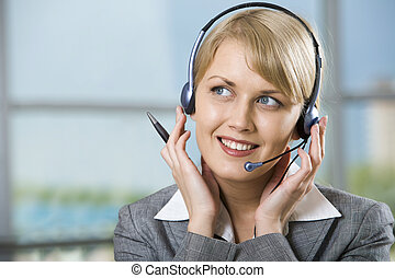 Talking by the headset - Portrait of beautiful smiling blond...