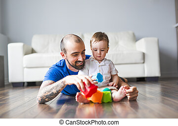 happy father and little son playing with toy blocks at home...