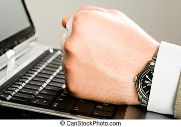 Fist - Image of human  fist on the keyboard of laptop