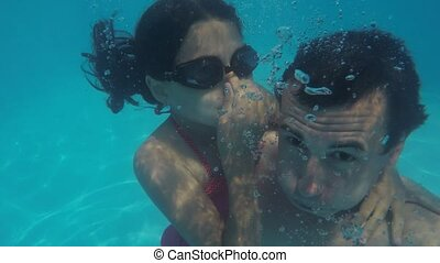 Dad and daughter in the pool underwater. man and girl...