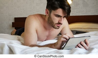 Young man lying in bed using tablet computer - Young...