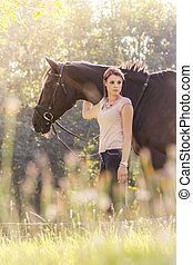 Wonderful young equestrian woman with horse in summer sun...