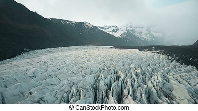 Beautiful aerial panoramic view of Vatnajokull glacier with ash. Copter flying over iceberg in national park in Iceland.