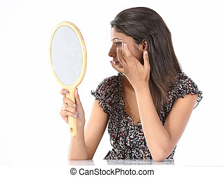 woman see her hairstyle in mirror