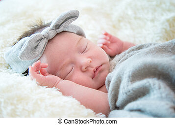 Newborn baby girl is sleeping on fur blanket