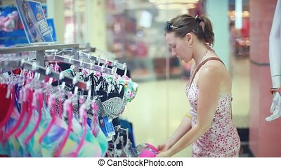 Young woman shopping for a swimsuit. 1920x1080