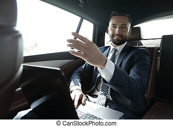 businessman sitting in the back seat in the car and pointing...