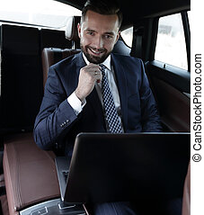Business people use a laptop in their car