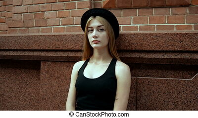 a charming young girl in a black t-shirt and hat stands near...