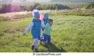 Happy children runs holding hands in the Park with balloons