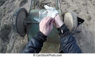 putting on work gloves. Person puts on a pair of worn work