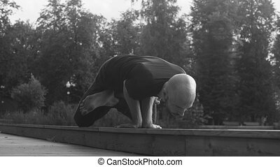 A man doing yoga exercises in the park - Black and white...