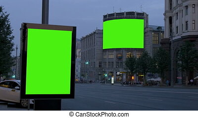 Two big billboards with a green screen. In the evening, on a busy street.