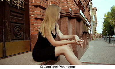 attractive young blonde sitting on the street in a black...