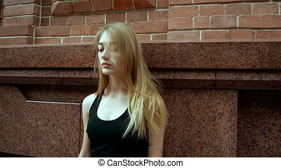 beautiful serious girl posing outdoors and straightens hair...