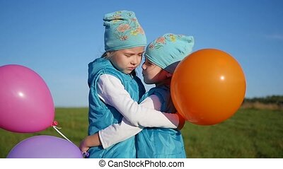 two twin sisters hugging and kissing. Children hold balloons