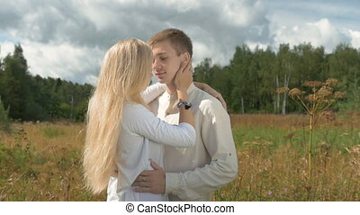 Young white couple on date. The girl gently caresses her boyfriend.