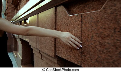a young girl walking down the street and holds your hand over the wall