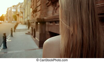 young girl with blond hair goes down the street close-up