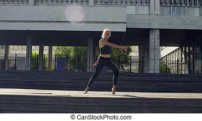 Young woman doing yoga exercises, against modern building at...