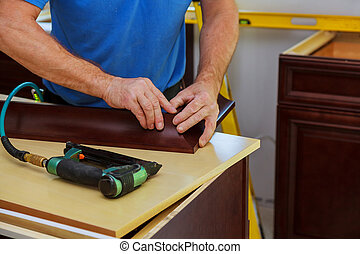 Carpenter brad using nail gun to Crown Moulding on kitchen...