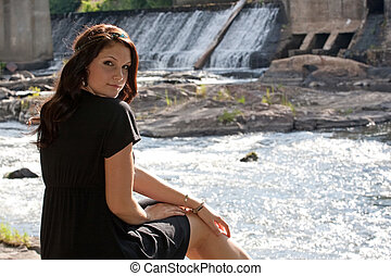 Brunette by the River - An attractive young woman wearing a...