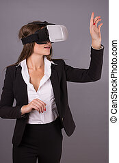 Business Woman in wearable technology VR glasses. Confident...