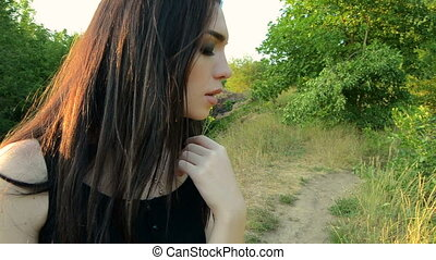 beautiful happy brunette stands outdoors with eyes closed...