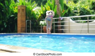 Young woman jumping swimming and swims up, out of pool in...