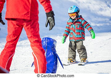 Young skier sliding down towards towards toy penguin and ski instructor