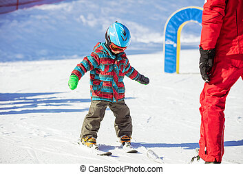 Young skier and ski instructor on slope in beginners' area
