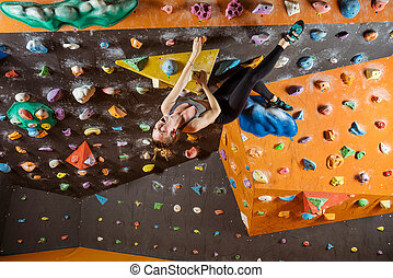 Expressive young woman bouldering in climbing gym,...