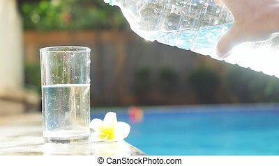 Water flowing into the glass near swimming pool and...