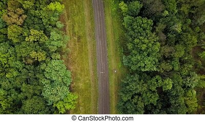 Flight over a railway surrounded by forest - View from...